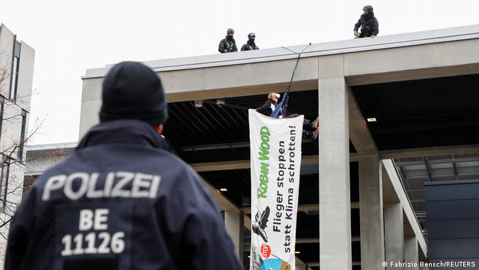 A climate activist dressed as a penguin holds a banner as he scales down from a roof during a protest against the official opening of the new Berlin-Brandenburg Airport