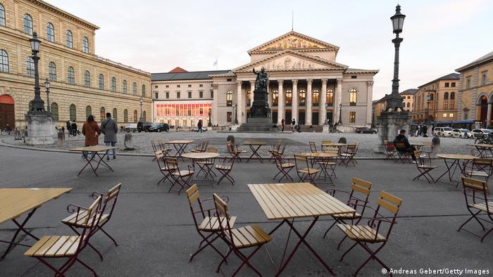 Здание оперного театра в Мюнхене и пустые ресторанные столики