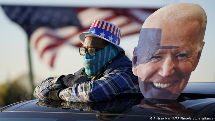 A man wearing a mask and a US-flag themed hat stands next to a giant cutout of Biden's face