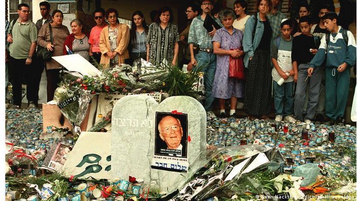Israelis behind a memorial of Yitzhak Rabin