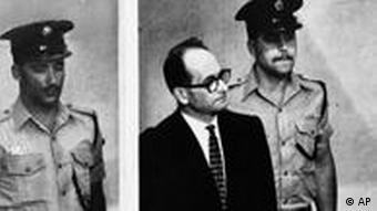 FILE - The 1962 file photo shows Adolf Eichmann standing in his glass cage, flanked by guards, in the Jerusalem courtroom where he was tried in 1962 for war crimes committed during World War II. The basics of Adolf Eichmann's story are well documented: Commonly known as the architect of the Holocaust for his role in coordinating the Nazis' policy of genocide, he fled Germany only to be captured in Argentina by the Mossad, taken to Israel for trial, and hanged. (AP Photo)