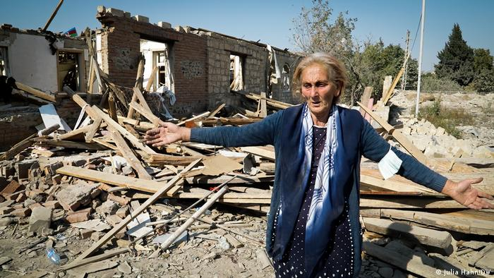 Ragiba Guliyeva in front of the rubble of her home