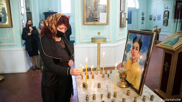 A woman lights a candle for a boy who was killed in the attack on Ganja