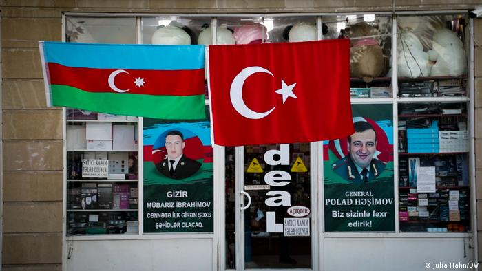 Turkish and Azerbaijani flags in front of a business with propaganda posters in the windows