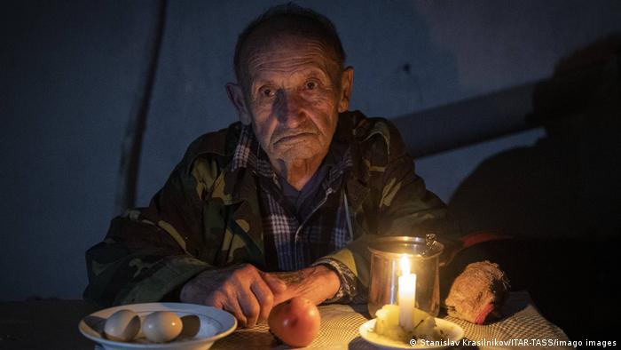 An elderly man in the dark, seated at a table with a lit candle and plates with boiled eggs, a tomato, bread