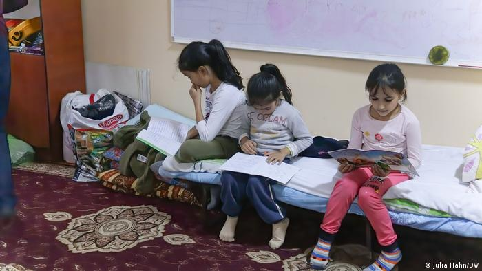Three young girls seated on a cot, reading, imn the Azerbaijani town of Barda