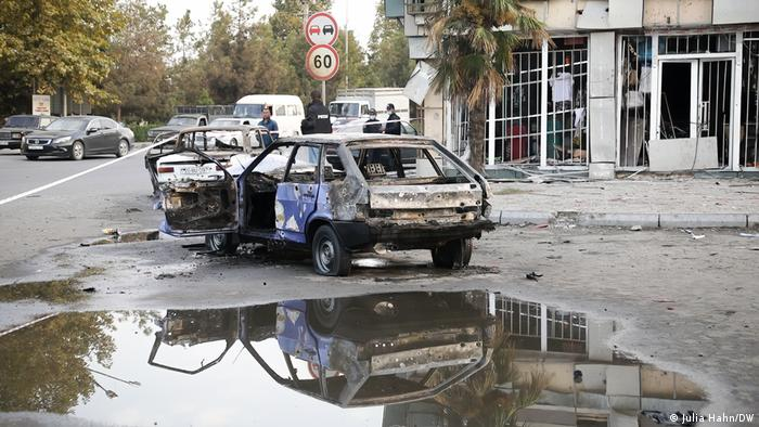 A burned-out car in front of a building with a shop that has been destroyed in Barda