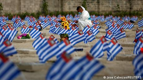 Dan mrtvih (Día de Muertos) obeležava se u mnogim zemljama Latinske Amerike, između ostalih i u Salvadoru. Ovaj radnik na groblju stavlja cveće i zastavice na grobna mesta onih koji su preminuli od posledica kovida 19. Prema podacima Univerziteta Džon Hopkins, do sada je u toj maloj zemlji od posledica korone umrlo skoro hiljadu ljudi.