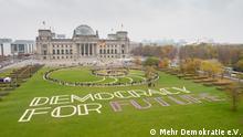 Die Teilnehmer des ersten Bürgerrates inszenieren sich als lebendiges Kunstwerk auf der Wiese vor dem Reichstag. Unterhalb der von Menschen gebildeten Rosette ist im Rasen der Schriftzug Democracy for Future zu sehen. Bildquelle: Mehr Demokratie e.V.