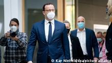 Jens Spahn geht mit Mund-Nasenbedeckung und Anzug mit einigen anderen Personen zur Bundespressekonferenz.
