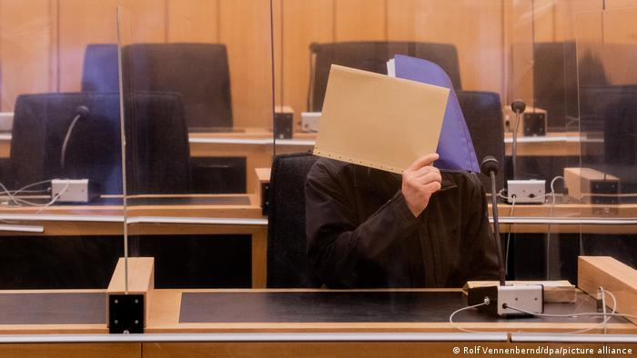 The defendant in a sexual abuse case in Münster, Germany shields his face from cameras