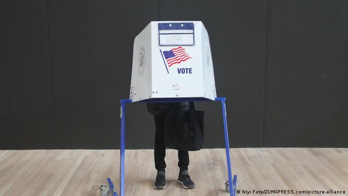 Человек в Нью-Йорке стоит в избирательной кабинке с флагом США