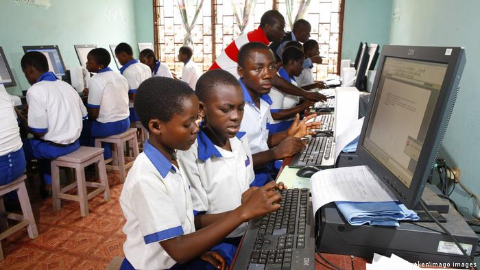 Children sitting in front of computers at a school in Cameroon