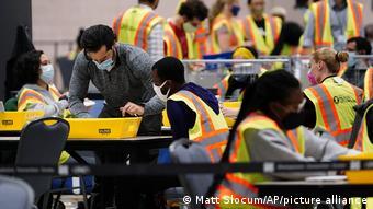 Люди обрабатывают избирательные бюллетени