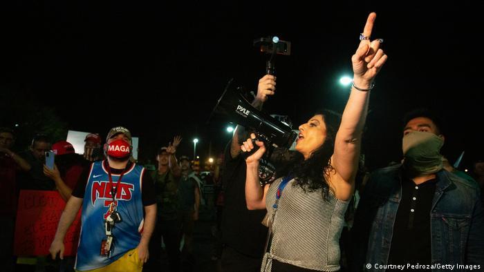 Mulher fala em megafone durante protesto
