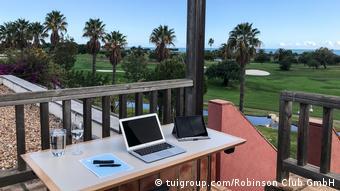 Компьютер на столе, стоящем на балконе на фоне пальм и моря