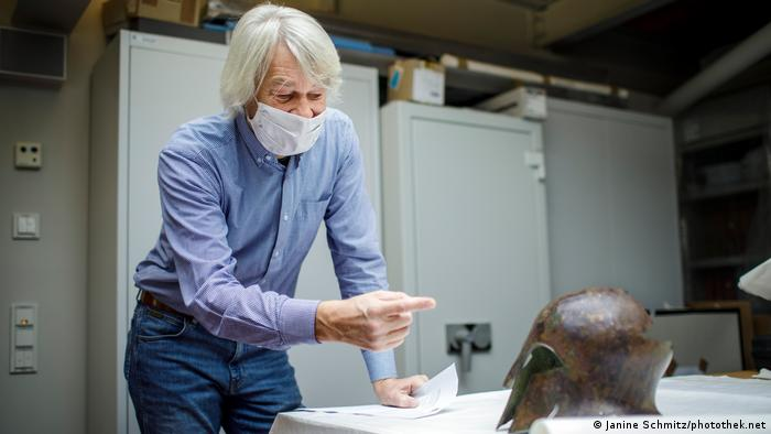 A man points at a bronze helmet sitting on a table