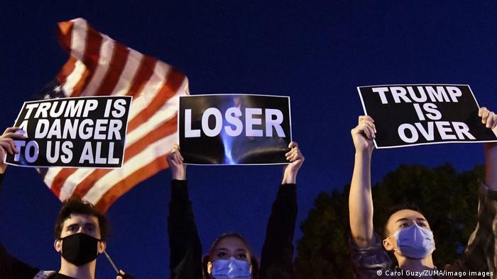 Três manifestantes de máscaras erguem cartazes em protesto em Washington