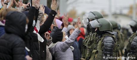 Демонстранты в Минске с поднятыми руками стоят перед силовиками в касках и бронежилетах