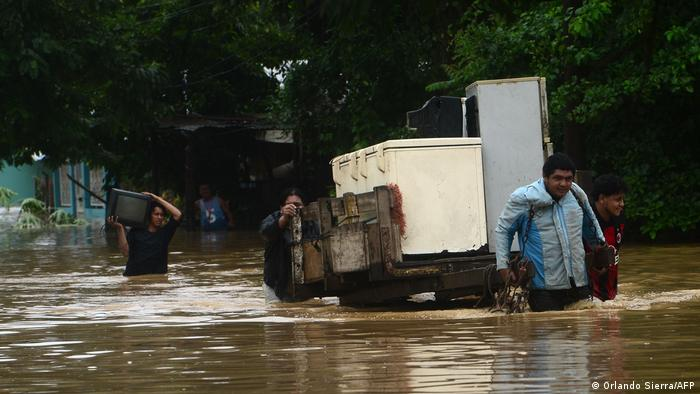 Local residents rescue their belongings after the overflowing of the Ulua River
