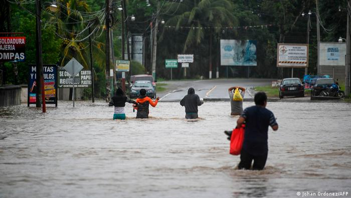 Residents walk in a flooded area due to the heavy rains caused by Hurricane Eta, now degraded to a tropical storm, at Las Posas village in Morales, Izabal, 220 km north Guatemala City