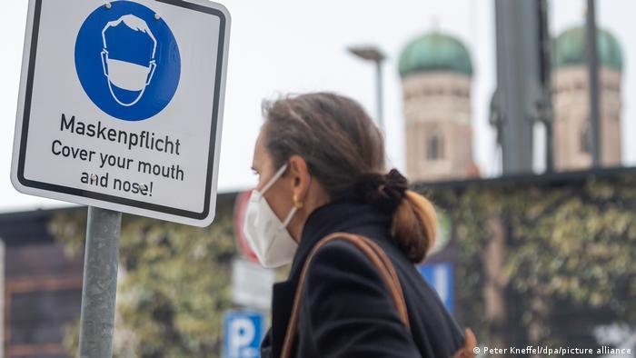Женщина в защитной маске рядом с уличным столбом с плакатом, напоминающим о необходимости надеть маску