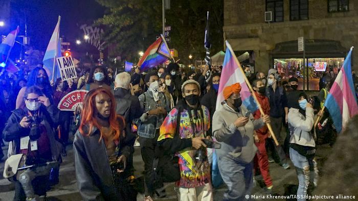 Pessoas com bandeiras coloridas durante manifestação noturna