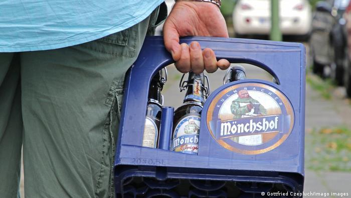 Foto de una persona con una caja de cervezas