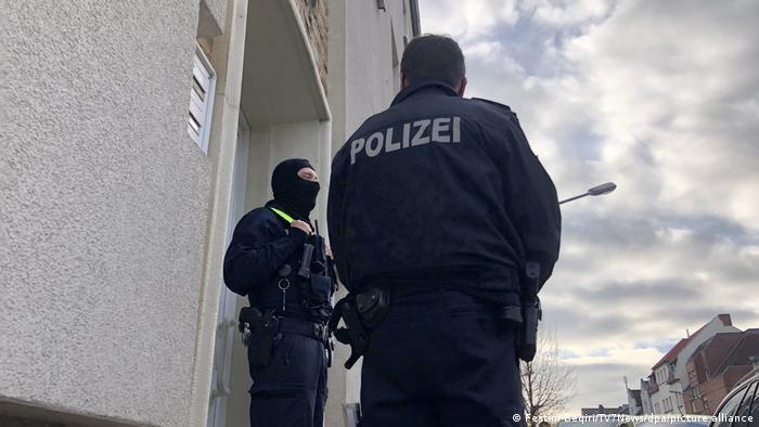 Dois policiais armados parados em frente a uma casa. Um deles está de costas e o outro, de lado. O policial que está de lado veste uma balaclava.