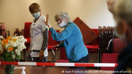 An elderly woman waves goodbye at a nursing home in eastern France