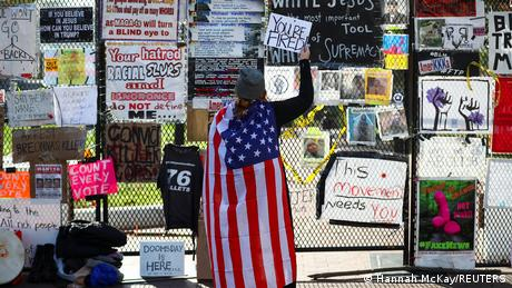 A person drapped in an American flag in front of a fence filled with posters