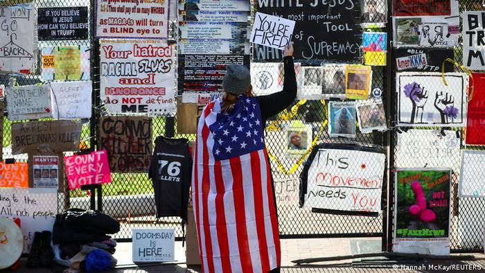 Pessoa vestida com a bandeira americana mexe em cerca cheia de cartazes