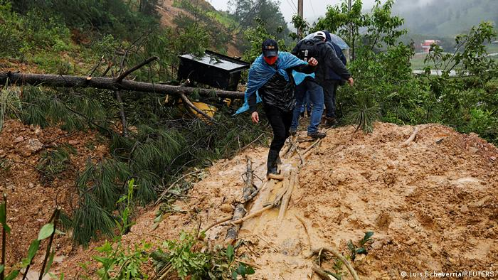 Two men crossing a mud hill after a mudslide in Guatemala