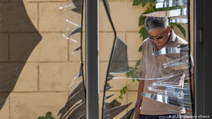 Man looking at broken window of China's embassy in Kyrgyzstan in 2016