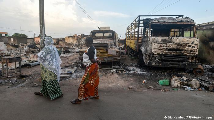 Women walk in a damaged street in Toumodi, central Ivory Coast