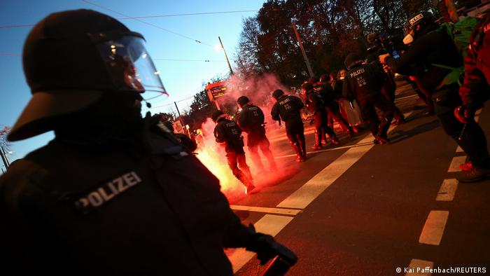 Flames can be seen in front of police officers on a street in Leipzig