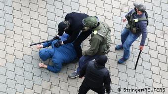 Люди с дубинками держат лежащего на брусчатке человека в Минске