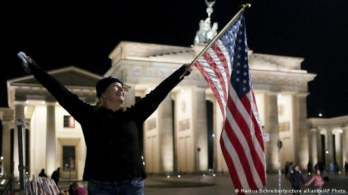 A joyful American woman waves a US flag in front of the Brandenburg Gate (Markus Schreiber/picture alliance/AP Photo)