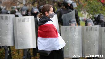 Девушка с бело-красно-белым флагом на фоне спецназовцев со щитами