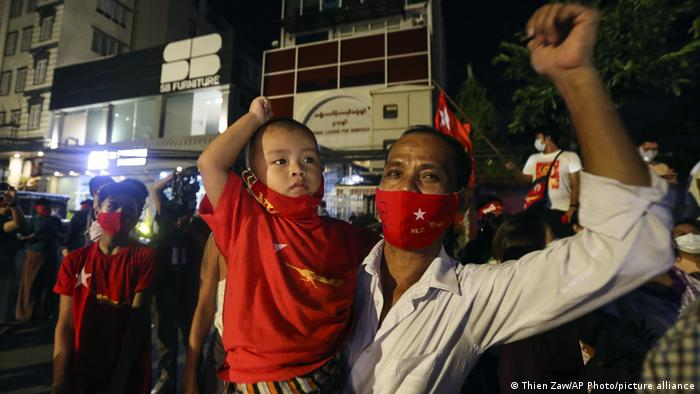 Supporters wearing face mask cheer as they gather in front of Myanmar Leader Aung San Suu Kyi's National League for Democracy