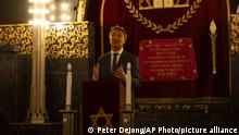 Rene de Reuver, speaking on behalf of the General Synod of the Protestant Church in the Netherlands, reads a statement at the Rav Aron Schuster Synagogue in Amsterdam, Netherlands, Sunday, Nov. 8, 2020.The Dutch Protestant Church made a far-reaching confession of guilt Sunday for its failure to do more to help Jews during and after World War II and even for the church's role in preparing the ground in which the seeds of anti-Semitism and hatred could grow. The statement came at a solemn ceremony to mark Monday's anniversary of the Nazis' anti-Jewish Kristallnacht, or Night of Broken Glass, pogrom in Germany and Austria. (AP Photo/Peter Dejong) |