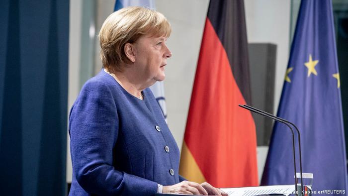 Angela Merkel de casaco azul ao microfone, com bandeiras da Alemanha e da UE ao fundo