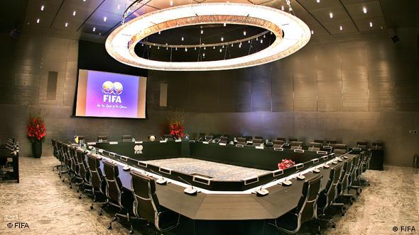 The table at which the executive committee meets is shown under a large oval light