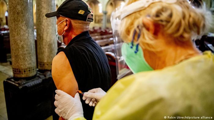 Enfermeira de máscara injeta vacina em braço de homem com máscara