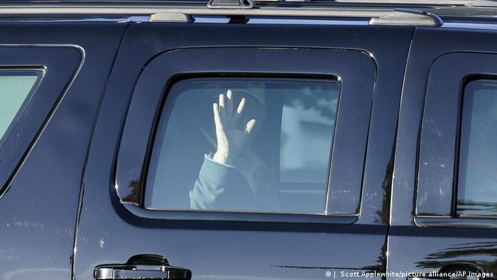 Donald Trump waves from his limo