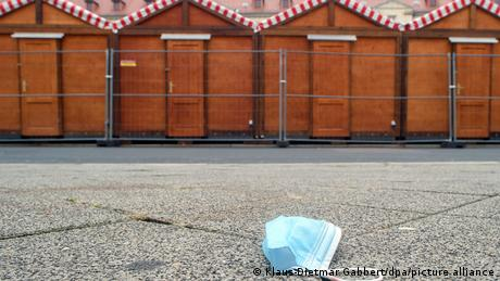 Discarded face mask and closed Christmas Market stalles