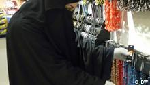 Das Bild zeigt eine vollverschleierte Frau mit dem Gesischtsschleier (Burka oder Niqab) beim Schmuckkauf in einem Schmuckladen in der Kölnerinnenstadt. Bildrechte: Hicham Driouich (DW-Volontär)