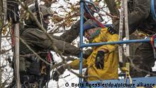 10.11.2020, Hessen, Niederklein: Ein Aktivist (gelbe Jacke) wird von Polizisten eines Spezialeinsatzkommandos SEK aus einem Baumhaus entfernt, in dem er sich verbarrikadiert hatte, und festgenommen. Derzeit halten Aktivisten den Dannenröder Forst besetzt und demonstrieren gegen den geplanten Ausbau der A49 und für den Erhalt des Waldstücks, das dem geplanten Ausbau zum Opfer fallen würde. Polizisten sind damit beschäftigt, die verschiedenen Barrieren zu räumen. Foto: Boris Roessler/dpa +++ dpa-Bildfunk +++ | Verwendung weltweit