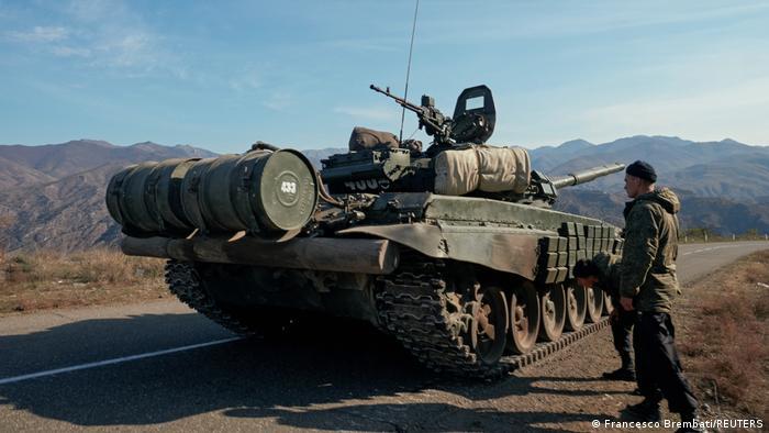 Russische Friedenstruppen stehen neben einem Panzer in Berg-Karabach