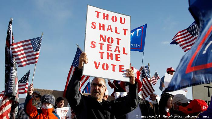 A Trump supporter holds a 'Thou Shalt Not Steal the Vote' sign